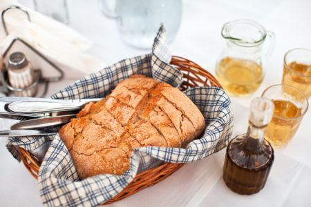 Homemade bread in greek taverna with olive oil and white wine